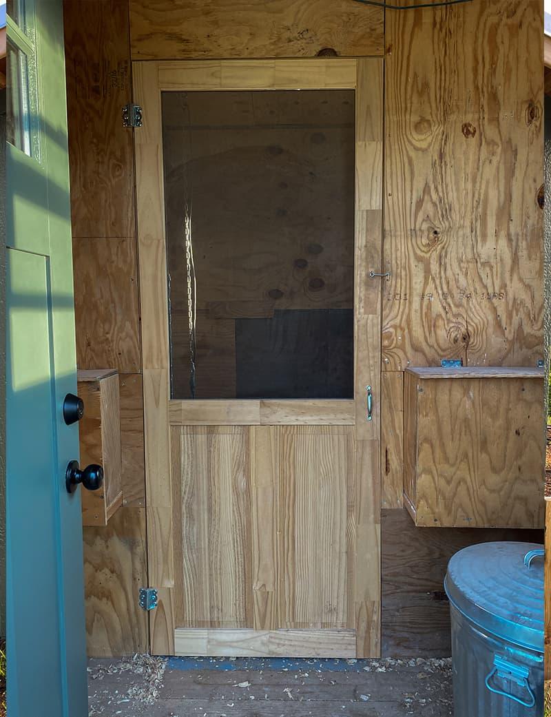 Interior of chicken coop with screen door for seperation