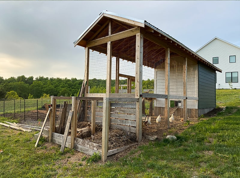 back of chicken coop with chicken run and compost bins