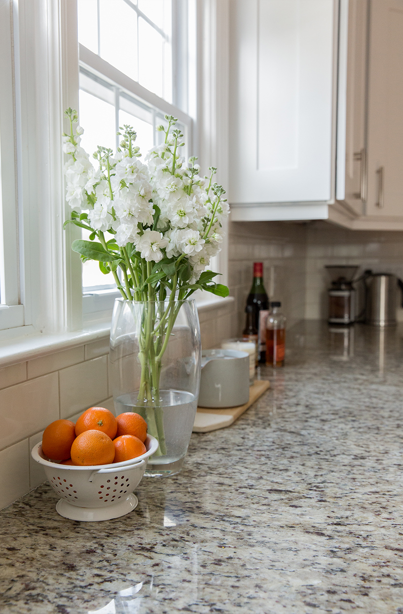 granite counter tops in a kitchen with flowers on the counter