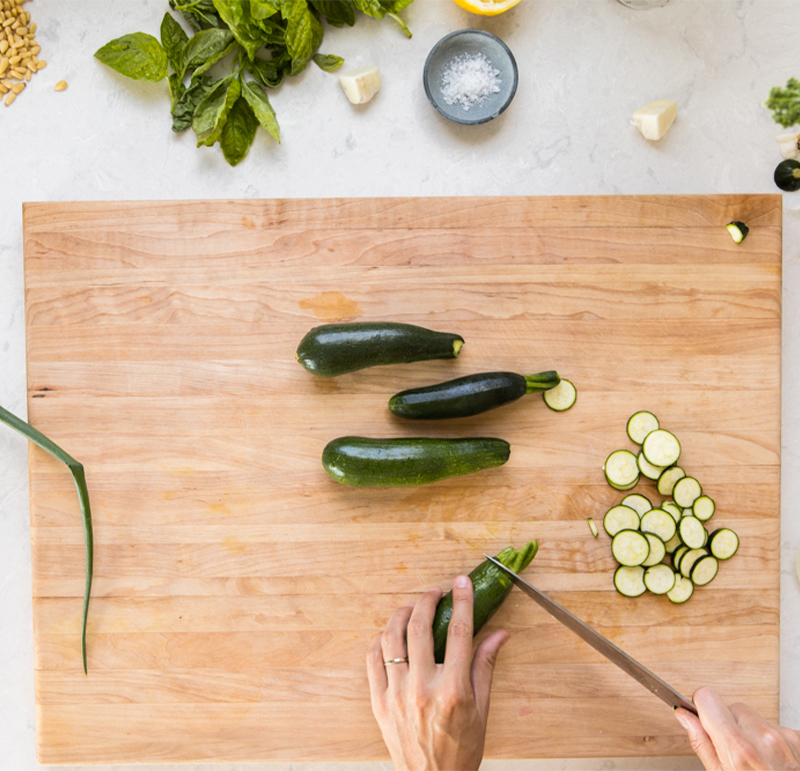 Thinly slicing zucchini to be cooked